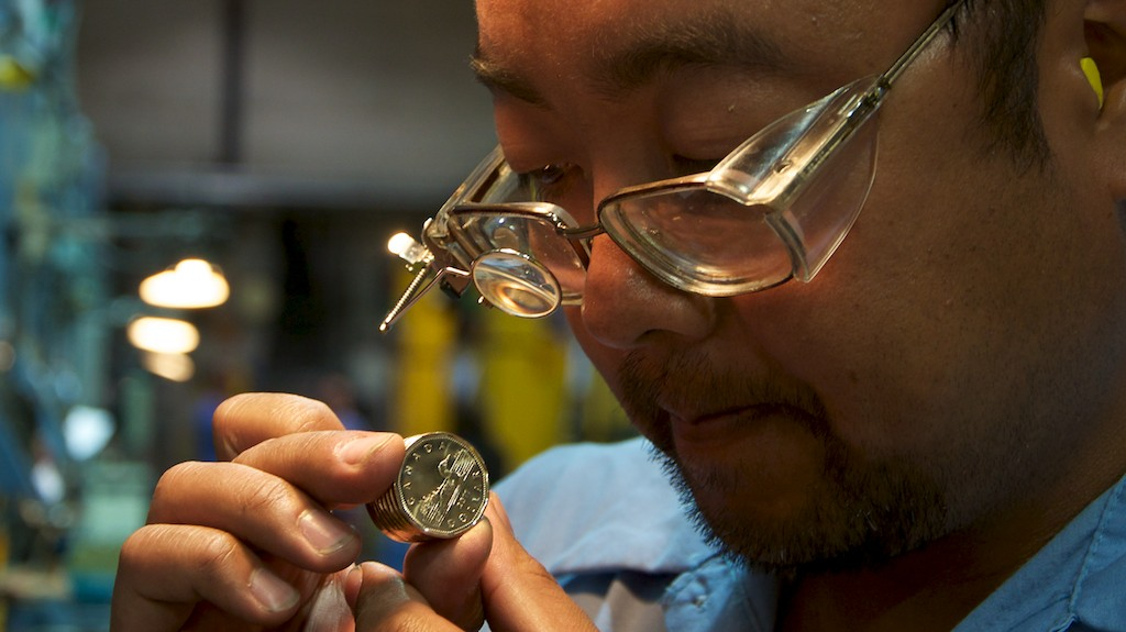 As coins are struck they are periodically inspected for imperfections.